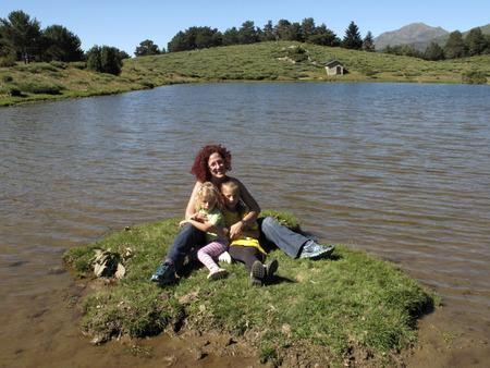 Family in the small lake of Vielha, Landscape near the tunnel of Vielha, road N 230, Vielha e Mijaran, Viella, Val dAran, Aran Valley, Pyrenees, Lleida province. View of mountains, town centre, river and Vielha small lake