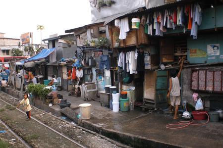 dwellings: People living along the railway. Maninal train Station.  Slum dwellings in Blumentritt Manila. Rail track and squatters at Blumentritt Manila.
