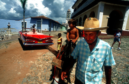 fifteen year old: Donkey trip in Trinidad for children. Classic red 1959 beautiful Chevy convertible on cobblestone street of Trinidad Cuba an old colonial village Editorial
