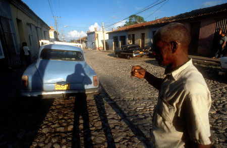 atraction: Colourful houses and people in a street scene. Classic American car parked on a street with traditional,in the background, Trinidad, Cuba, West Indies, Central America Editorial