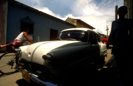 national historic site: Colourful houses and people in a street scene. Classic American car parked on a street with traditional,in the background, Trinidad, Cuba, West Indies, Central America Editorial