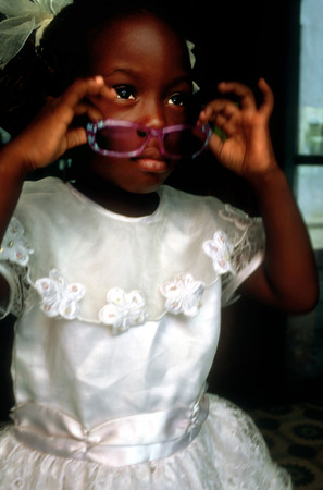 headress: Little girl in Sunday best clothes on step in the street Havana Cuba