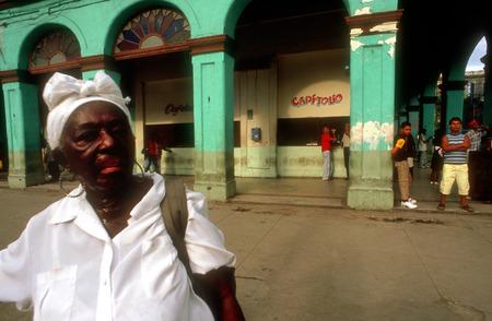 slaves: Woman santera passing the Capitolio Nacional, Havana, Cuba. Santería, also known as Regla de Ochá or La Regla de Lucumí is a syncretic religion of Caribbean origin which developed in the Spanish Empire among West African slaves. Santería is influenced Editorial