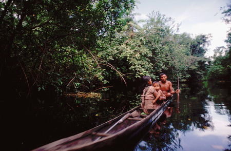 dugout: Warao Indians in a dugout canoe, Orinoco River Delta, Venezuela, South America. The Warao are an indigenous people inhabiting northeastern Venezuela and western Guyana. Alternate common spellings of Warao are Waroa, Guarauno, Guarao, and Warrau. The term