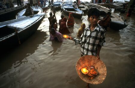 street creed: Boy selling flowers and deepak (floating flowers and oil lamp) in Varanasi, India. Varanasi, Uttar Pradesh, India. For most of the year you can walk freely along the whole length of the ghats, although during and immediately after the monsoon the water le