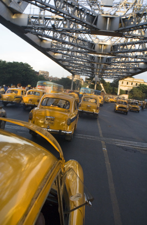 hooghly: Yellow Ambassador taxis (cabs) crossing Howrah Bridge in Kokata (Calcutta), India. Kolkata, West Bengal, India. The taxi is one of the few nostalgic icons that represent Kolkata. Countless love-tours, many a sight-seeing around the city of joy has been in