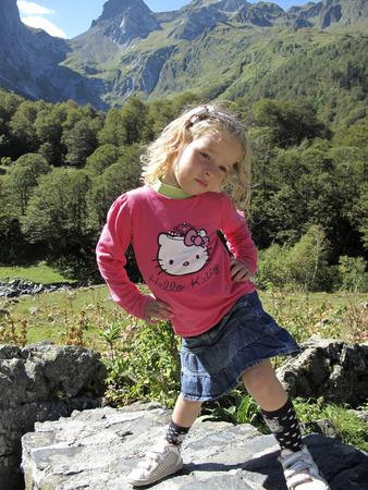 spanish looking: Girl in a landscape near the tunnel of Vielha, road N 230, Vielha e Mijaran, Viella, Val dAran, Aran Valley, Pyrenees, Lleida province. View of mountains, town centre, river and Vielha small lake