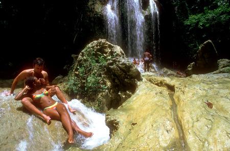 soroa: Couple: foreigner and cuban nice girl in bathing suits sitting at the waterfall Salto del Arco Iris Soroa Cuba
