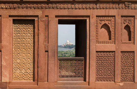 encompasses: Agra, Uttar Pradesh, India. Taj Mahal- As Seen from Agra Fort Window. Near the gardens of the Taj Mahal stands the important 16th-century Mughal monument known as the Red Fort of Agra. This powerful fortress of red sandstone encompasses, within its 2.5-km