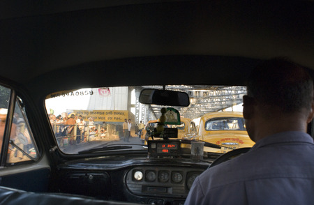 hooghly: Inside a Yellow Ambassador taxi (cab) crossing Howrah Bridge in Kokata (Calcutta), India. Kolkata, West Bengal, India. Kolkata, West Bengal, India. Kolkata: One of the most favored means of public transport in Kolkata, the taxis, have completed a hundred  Editorial
