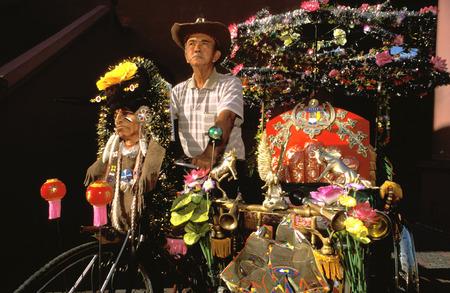 trishaw: Trishaw Ride driver in Malaka, Malaysia.  Tourists on trishaw ride in Melaka, Malaysia, are a popular tourist attraction.