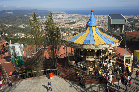 sharply: Carrousel, Tibidabo, Barcelona. The Tibidabo theme park, Barcelona, Spain. Tibidabo is a mountain overlooking Barcelona, Catalonia, Spain. At 512 meters it is the tallest mountain in the Serra de Collserola. Rising sharply to the north-west, it affords sp