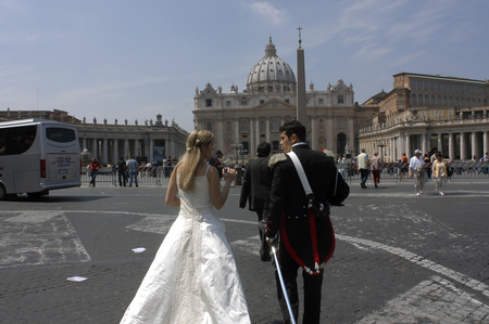 basillica: A bride and groom walk through St Peters Square in Vatican City, Italy.