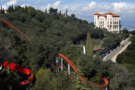 sharply: Roller coaster in The Tibidabo theme park, Barcelona, Spain. Tibidabo is a mountain overlooking Barcelona, Catalonia, Spain. At 512 meters it is the tallest mountain in the Serra de Collserola. Rising sharply to the north-west, it affords spectacular view