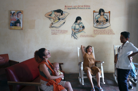 Expectant mothers sit on a porch of a maternity unit in Vinales, Cuba