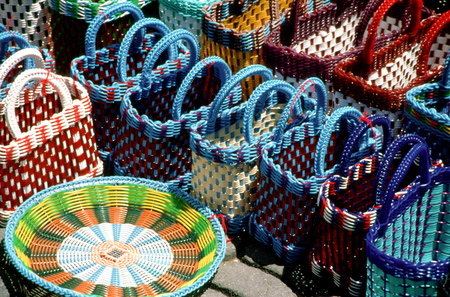 Stacks of colorful handmade woven baskets on display at a Mexican market in the Zocalo of Oaxaca, Mexico.
