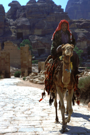 Bedouin guide with a camel in the colonnaded street, Petra, Jordan.