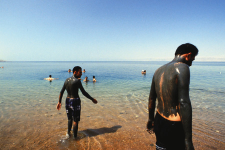 People covered with mud and swimming at the dead sea, Jordan Editorial