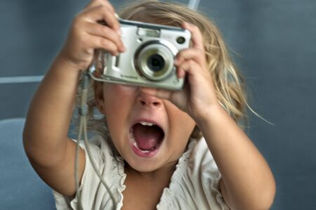 A two year old girl holding a digital snapshot camera and smiling.