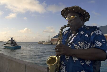 Musician playing the saxophone near of the port of Nassau, New Providence Island, Bahamas, Caribbean. 에디토리얼