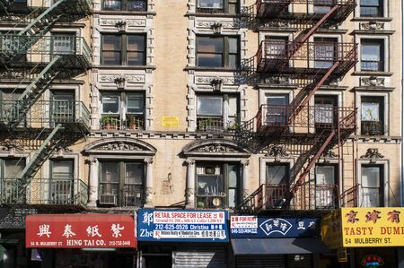 Building facades with fire escapes in China Town, New York City, USA.
