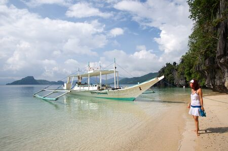 A tourist girl and a boat in the beach next to Cudugman cave. Bacuit archipelago. Palawan. El Nido. Philippines. There are still some pirate bones that haunted the area. 에디토리얼