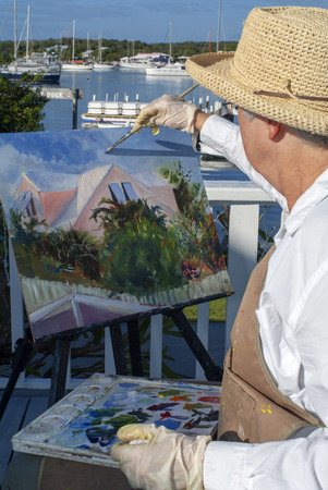 Woman painter painting the Hope Town Harbour. Hope Town, Elbow Cay, Abacos. Bahamas Editorial
