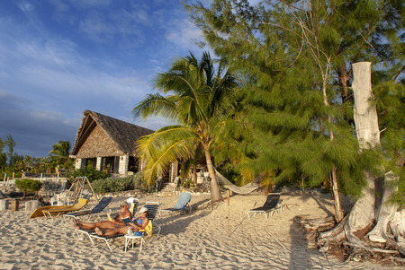 Cat Island, Bahamas. Beachfront cottages. Hotel Fernandez Bay Village resort. Tourists relaxing on the beach. 新聞圖片