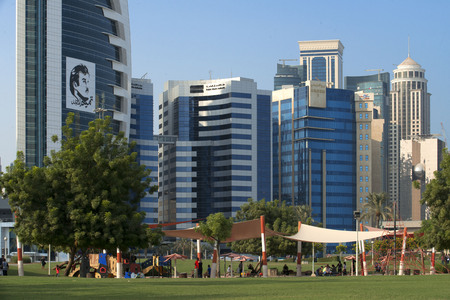 Child play area and modern skyline of the West Bay central financial district, Corniche promenade at Sheraton park Doha, Qatar, Middle East