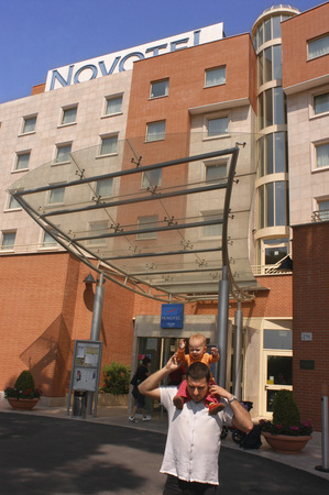 Tourist with a baby at the entrance of Novotel Roma.