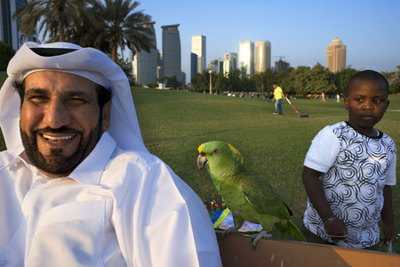 Local man with a parrot and modern skyline of the West Bay central financial district, Corniche promenade at Sheraton park Doha, Qatar, Middle East