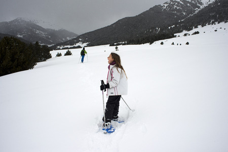 Baqueira Beret, Ski resort, Pyrenees, Aran Valley, Lleida, Catalonia, Spain. Children walking with snow rackets towards the summit of a snowy hill. Editorial