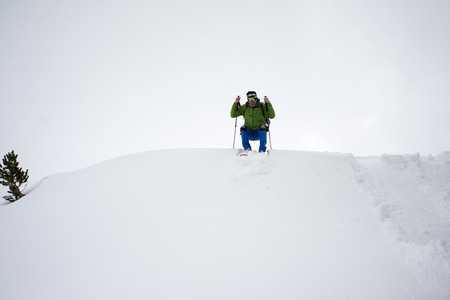 Baqueira Beret, Ski resort, Pyrenees, Aran Valley, Lleida, Catalonia, Spain. People walking with snow rackets towards the summit of a snowy hill.
