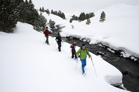 Baqueira Beret, Ski resort, Pyrenees, Aran Valley, Lleida, Catalonia, Spain. Line of people walking with snow rackets towards the summit of a snowy hill.