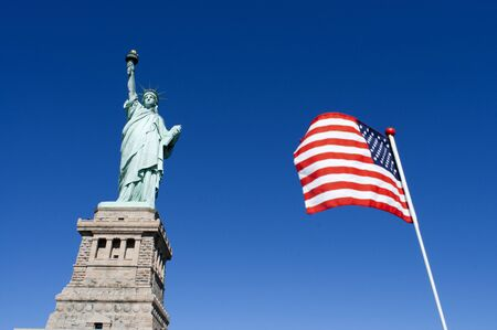 Statue of Liberty and american flag, Liberty Island, New York City, New York.