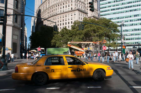 In Battery Park City, Manhattan, a taxi waits for passengers. Some New York City taxi cabs carry advertising on their roofs. View of buildings and taxi in West Street / Hudson River Greenway from Battery Pl/ Battery Park, Lower Manhattan, New York City.