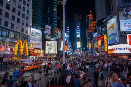 Bright neon signage flashes over crowds and taxi traffic zooming past Times Square the venue of the city's famous New. Mac Mc donald's Times Square New York City Editorial