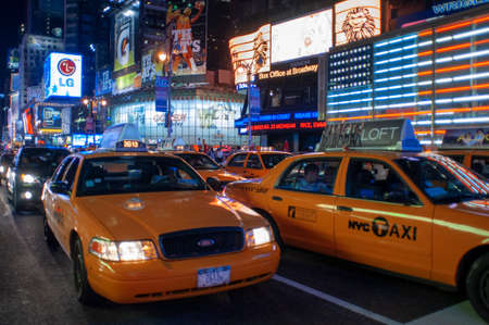 Yellow Cabs at the Times Square in New York. New york usa new york Times square busy crowded with tourists manhatten New york USA America United states of america. Bright neon signage flashes over crowds and taxi traffic zooming past Times Square the venu Editorial