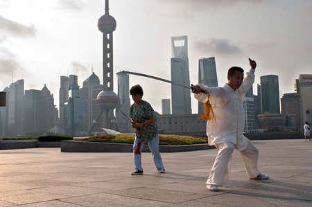 China, Shanghai, morning tai chi exercise on The Bund. Shanghi Bund : Early morning tai chi exercises with swords on the Bund in Shanghai China. The best taichi lessons I've had were from an old guy who practiced outside at 7am every morning. I learned 4  Editorial