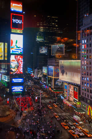 Bright neon signage flashes over crowds and taxi traffic zooming past Times Square the venue of the city's famous New.