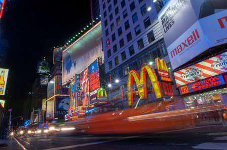 Bright neon signage flashes over crowds and taxi traffic zooming past Times Square the venue of the city's famous New. Mac Mc donald's Times Square New York City