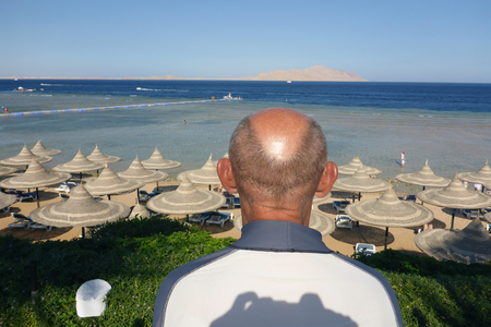 observes: the man observes overseas and the beach