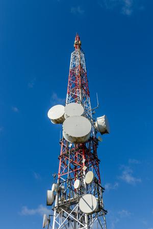 image of cellular antennas against a blue sky