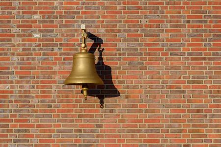 imagof bell hanging on a brick wall