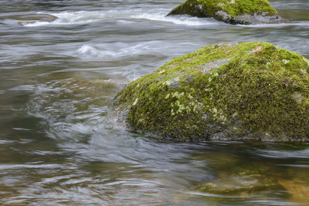 image of rock covered with moss on the river, blurred motion