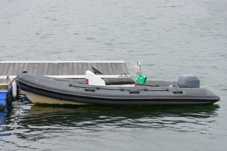 image of black inflatable motor boat at the wooden pier
