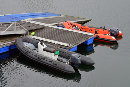 image of inflatable motor boat moored at a wooden piers