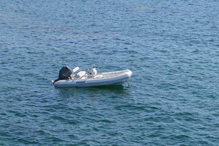 image of inflatable motor boat at sea at anchor