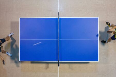 image of players playing on a blue tennis table, top view blurred motion Stock Photo