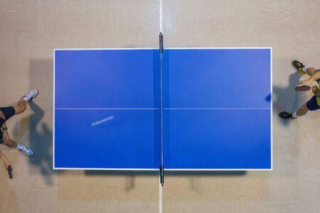 Imagen de jugadores jugando en una mesa de tenis azul, vista superior movimiento borroso Foto de archivo
